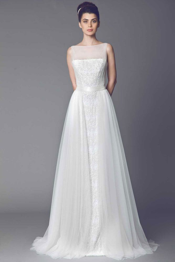 Veronica - Off White A line gown in embroidered Tulle with sheer neckline and a belted waist, draped Tulle on the sides.