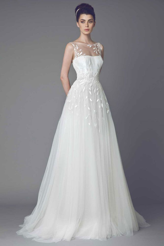 Daisy - Off White gown in Tulle with a sheer neckline and a scale liked sequined bust and cascading leave shaped embroideries on the waist.