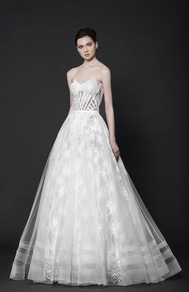 Off-White Lace gown with a sweetheart shaped bust corseted with wires, featuring a Tulle overskirt.