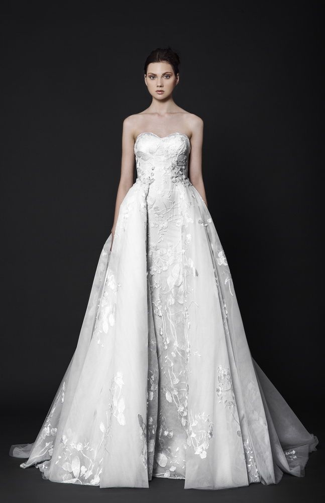 Off-White Tulle gown with a sweetheart shaped bust and an overlay skirt featuring floral embroideries.
