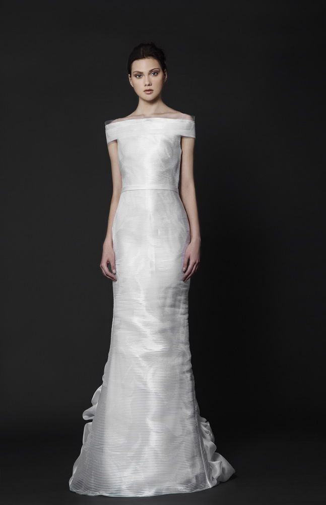 Off the shoulder floor-length dress in White Organza with bateau neckline and a ruffled train at back.