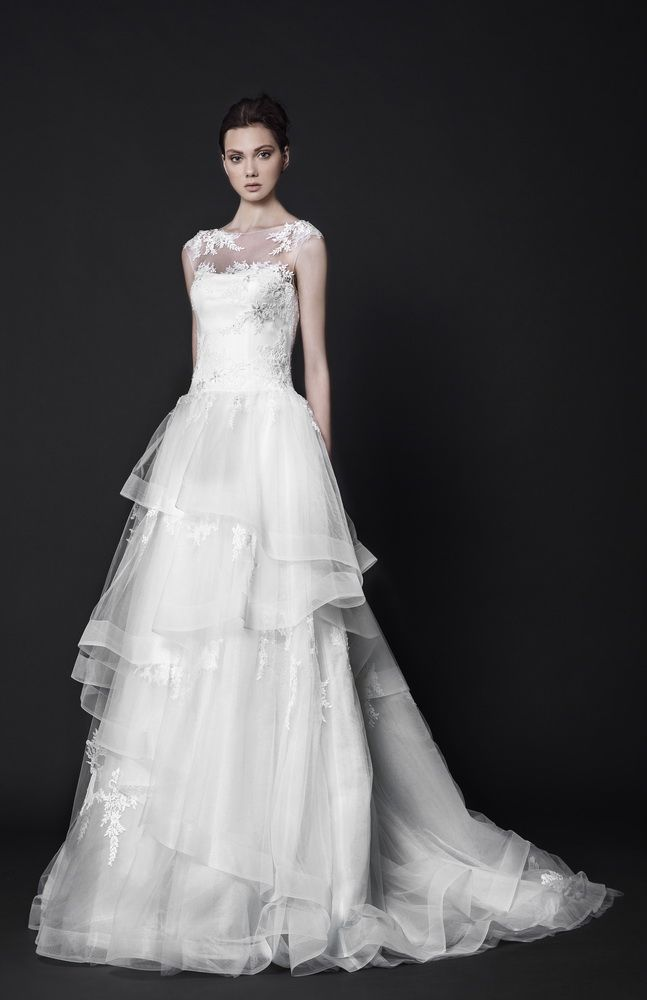 Off-White ball gown made of Tulle featuring a full ruffled skirt with crinoline hemline and delicate Lace appliques on the bust and shoulders.