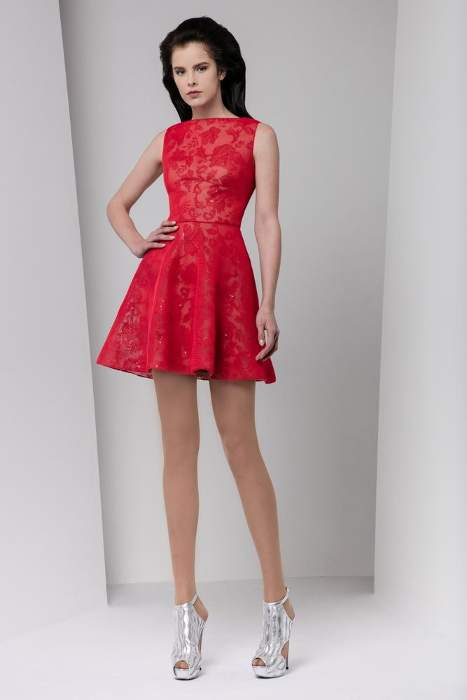 Short crimson tulle dress with wavy skirt and bateau neckline, embellished with a sequined flower pattern.