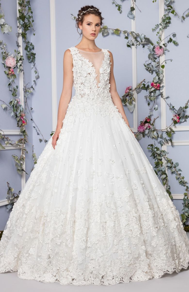 Off White princess Tulle gown with V-neckline, embellished with floral applique embroidery.