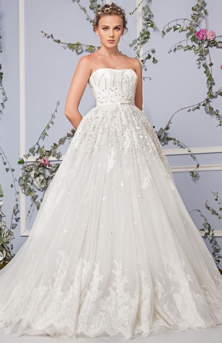 Strapless Off White Tulle dress with an embroidered bodice, a Tulle hemline and a belt on the waistline.