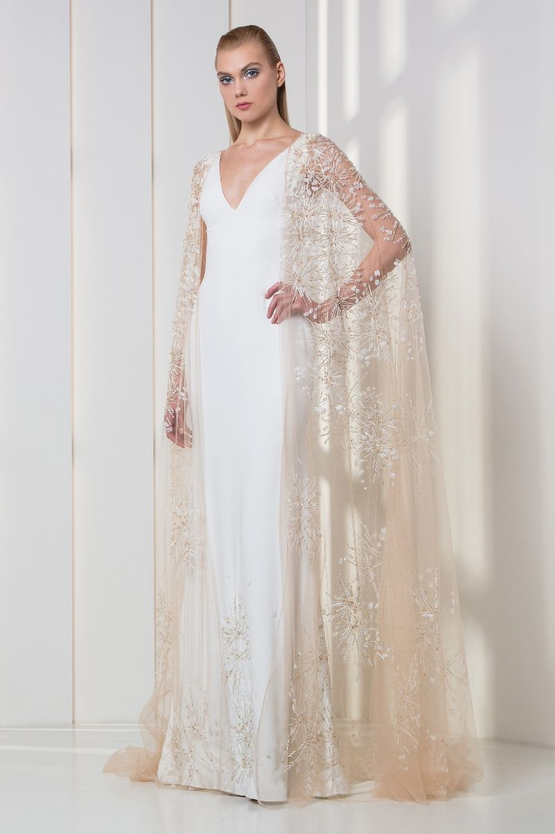 White crepe dress with V-neckline, with sequins embroideries on the hemline and a nude embroidered cape.