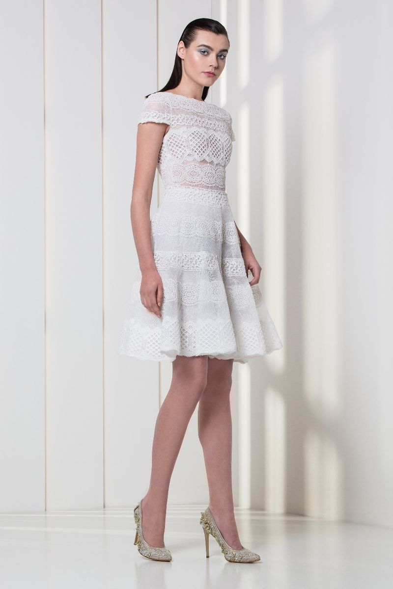 White lace cocktail dress with a flounced skirt and cap sleeves.