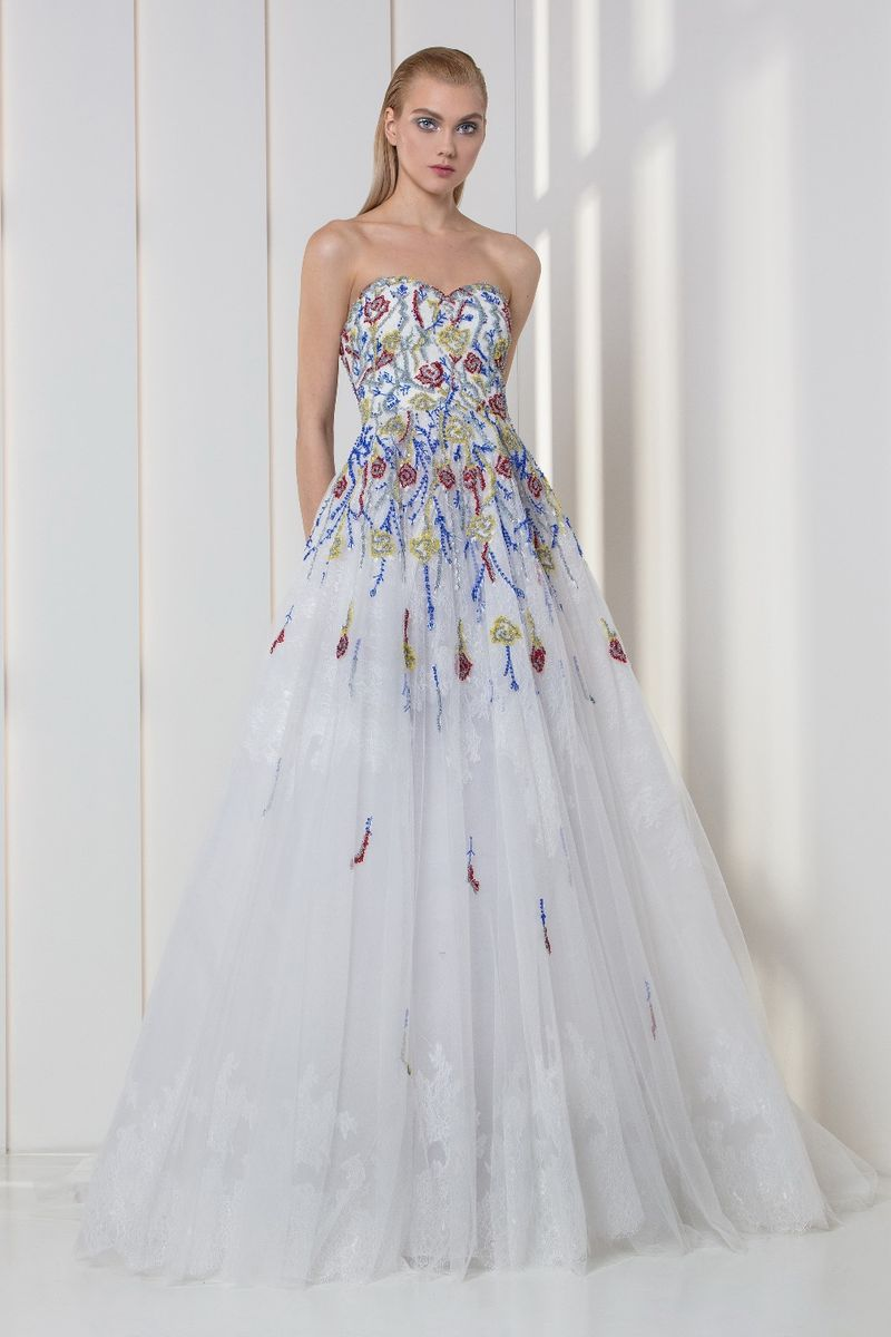 White sweetheart A-line dress in tulle and lace, featuring a strapless bodice embroidered with red, blue, yellow and silver crystals and sequins.
