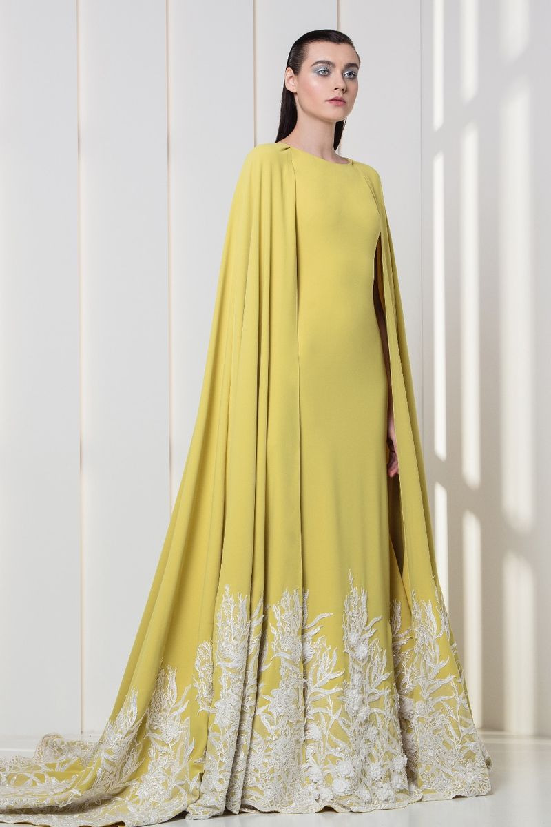 Amber yellow crepe dress with cape, featuring white flower appliques on the hemline.