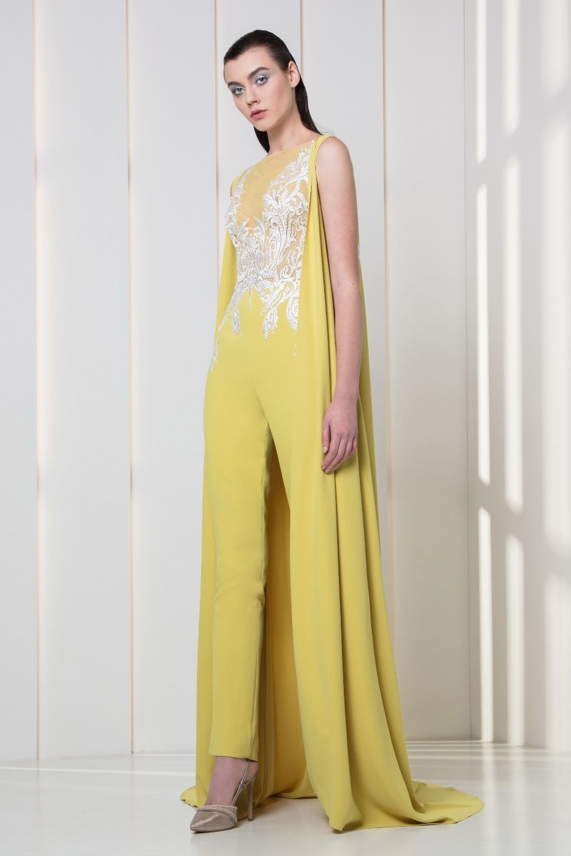 Amber yellow crepe jumpsuit with silk embroidery on the bodice and a sleeveless cape.