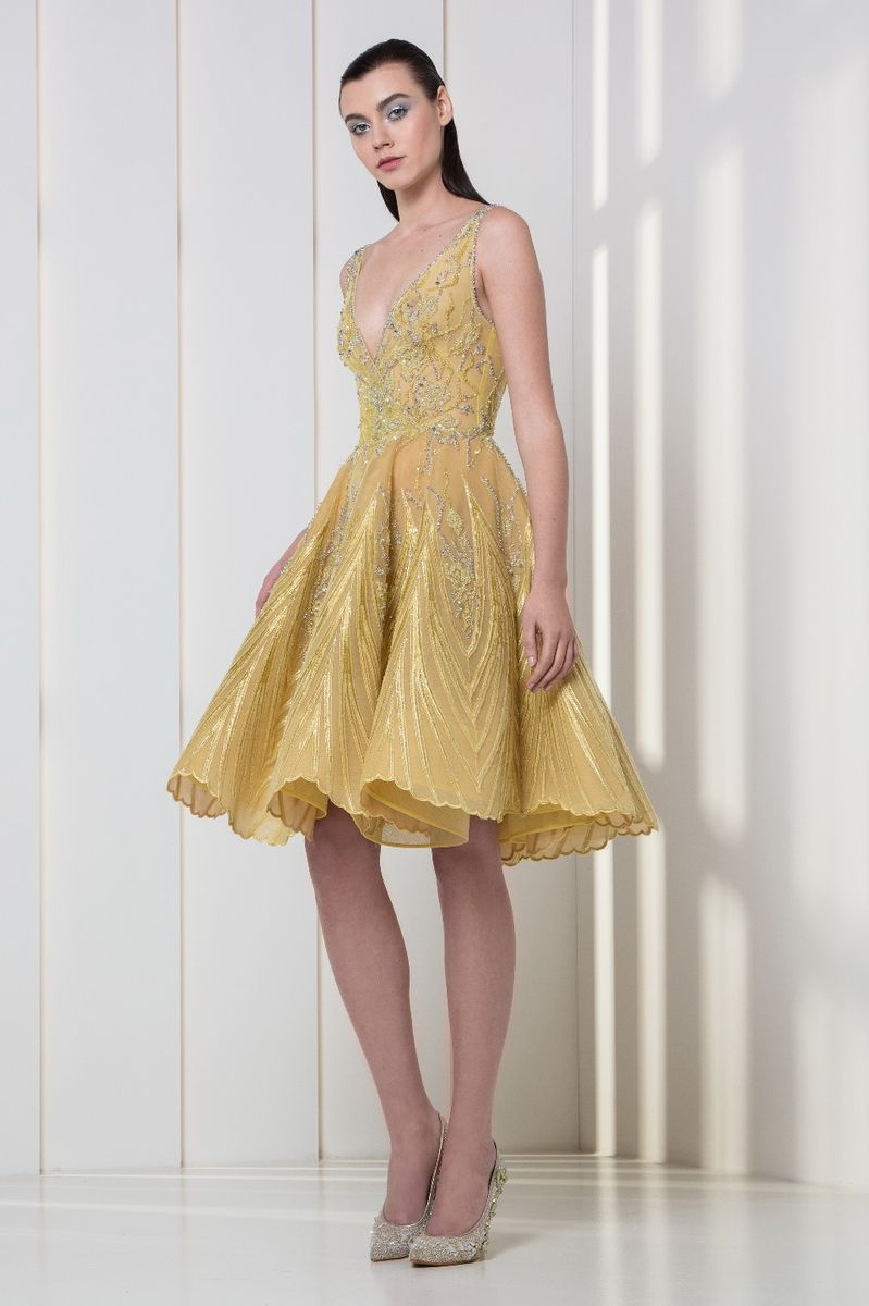 Yellow tulle and lace dress with a wrap bodice, featuring silver and gold sequins embroideries and a flounced skirt.