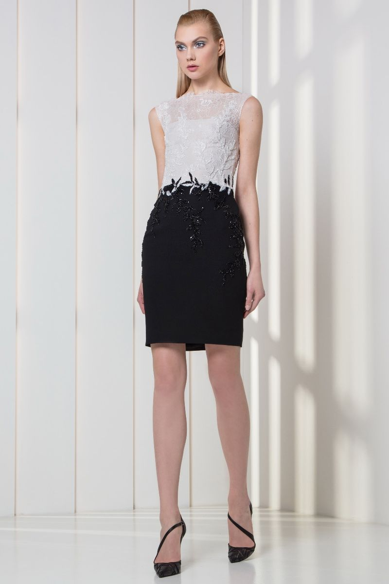 Black and white cocktail dress featuring an embroidered bodice and a crepe skirt.