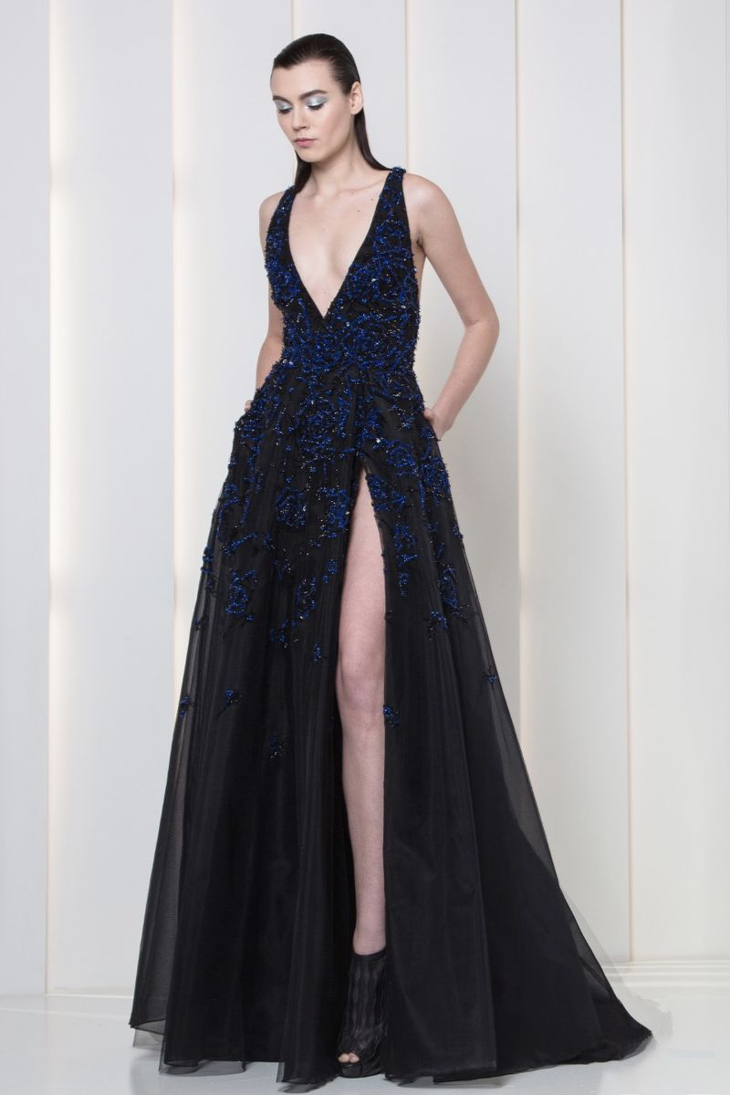 Charcoal black evening dress with V-neckline, a side slit and blue and black embroideries.