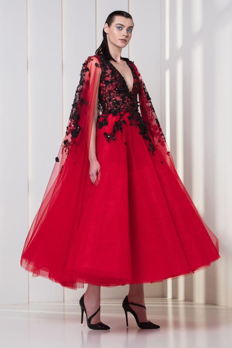 Midi-length red dress in embroidered tulle, with black flowery embellishments and a cape.