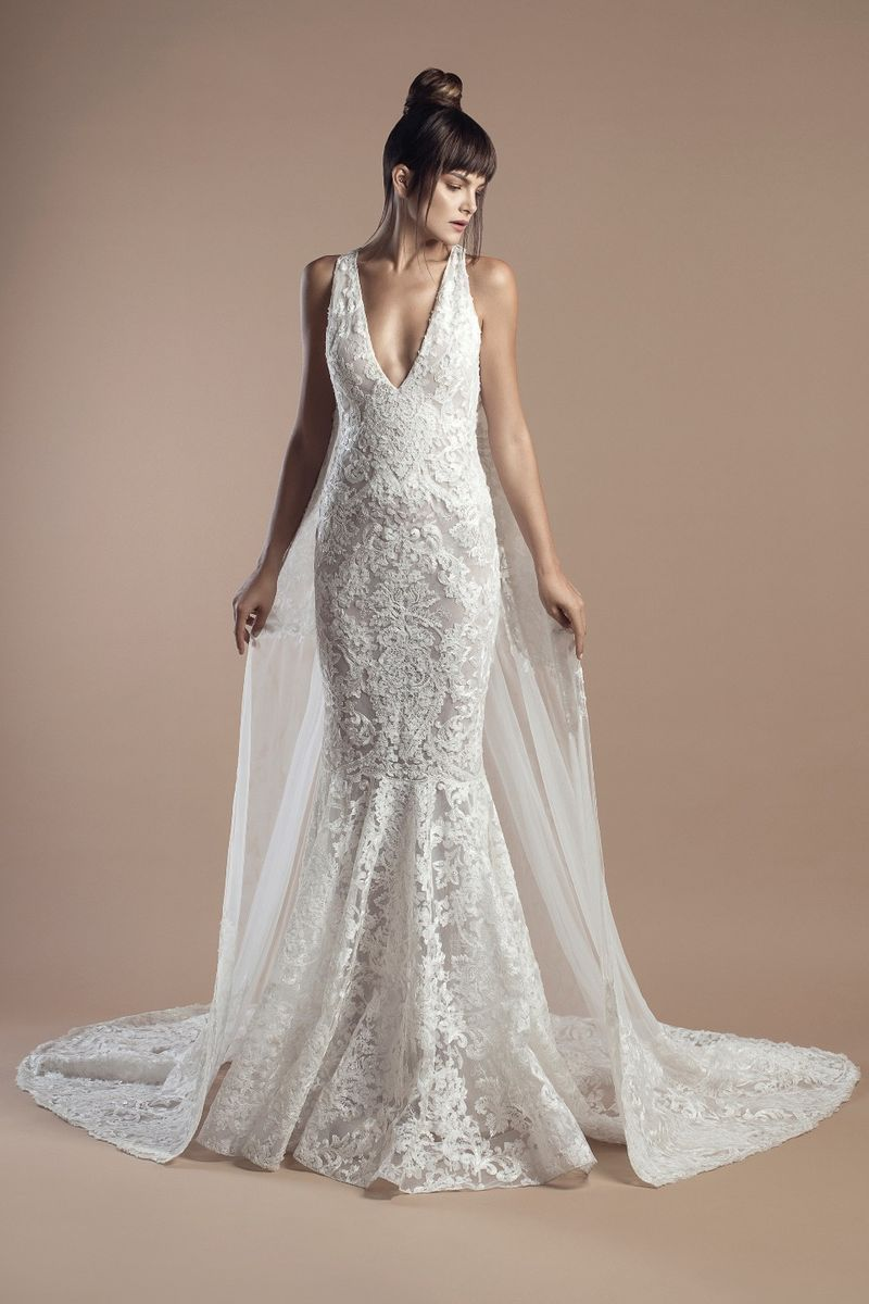 Off white lace mermaid dress, with V-neckline and a cape.
