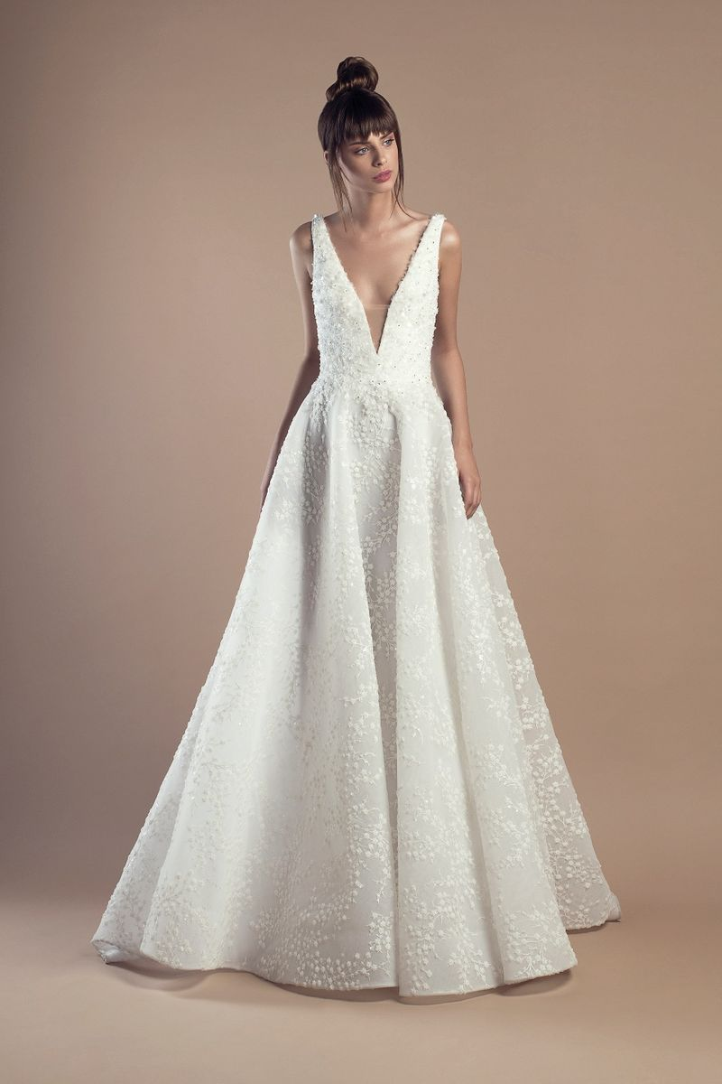 Off white A-line dress in organza and embroidered tulle, with deep V-neckline and a Court train.
