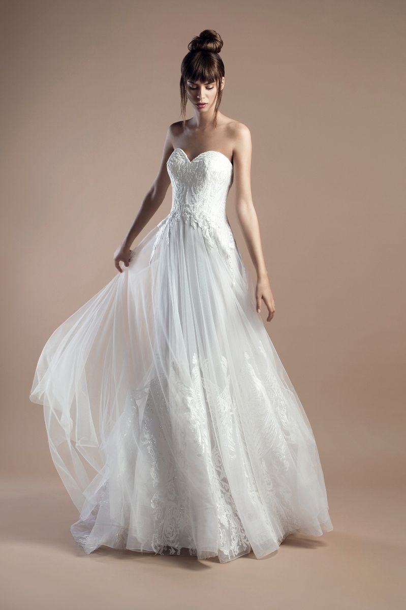 Off white strapless sweetheart dress made of tulle and silvery guipure appliques, with a Chapel train.